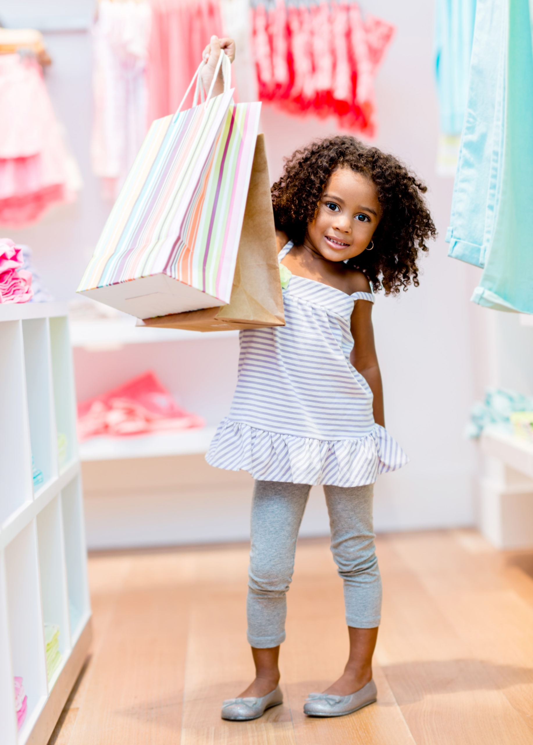 Cute,Little,Girl,With,Shopping,Bags,At,The,Store